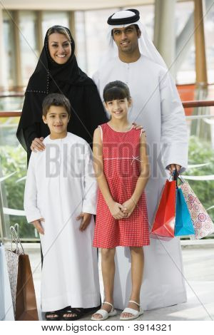 Middle Eastern Family Stood In Shopping Mall With Bags
