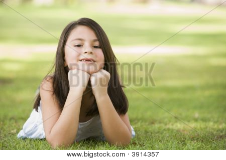 Middle Eastern Child Laying On Grass In Park