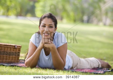 Middle Eastern Woman Laid On Picnic Blanket In Park