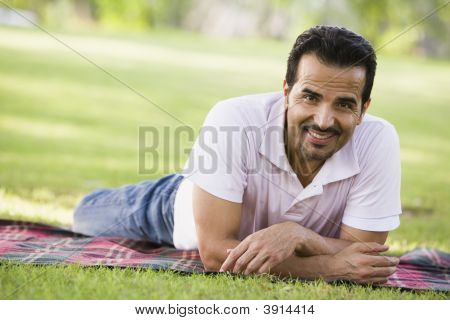 Middle Eastern Man Laid On Picnic Blanket In Park