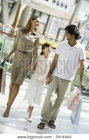 Middle Eastern Family Walking Through Shopping Mall With Bags