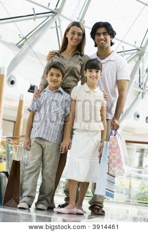 nahöstlichen Familie Standing in Shopping-Mall mit Taschen