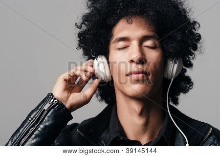 portrait of a dj man listening to music on headphones with afro hairstyle isolated on grey background