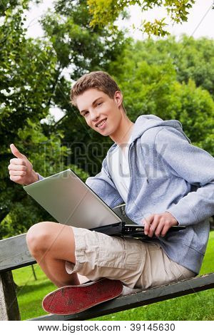 a teenager with laptop outdoors. sitting in the park mobile internet