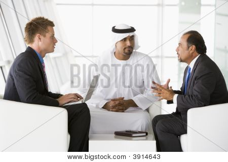Middle Eastern And Western Men Discussing Business