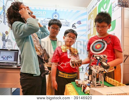 SUBANG JAYA - NOVEMBER 10: A visitor tries to interact with a robot created by unidentified students from Singapore at the World Robot Olympaid on November 10, 2012 in Subang Jaya, Malaysia.