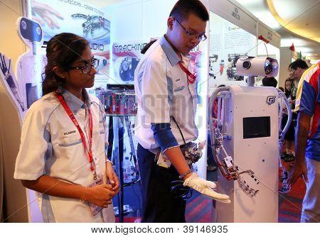 SUBANG JAYA - 10 de novembro: Um estudante não identificado da Malásia mostra que a mão do robô imita os dedos