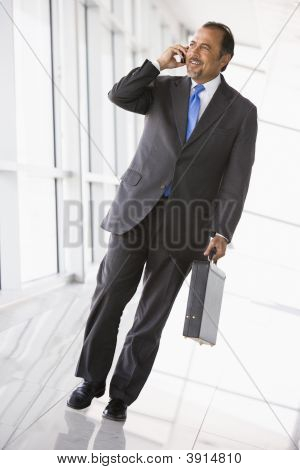 Middle Eastern Business Man Walking Down Corridor On Cell Phone