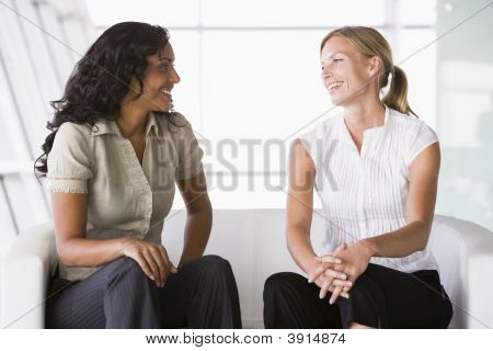 Middle Eastern / Western Business Women Sat On Sofa