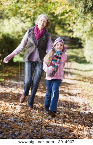 Girl And Grandmother Running Through Woodland