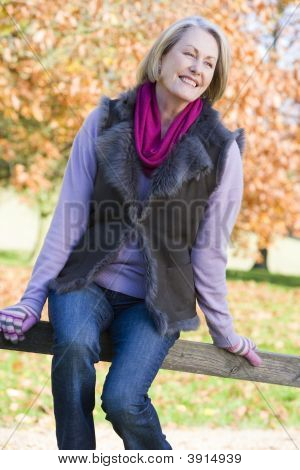 Woman Sat On Woodland Fence