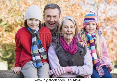 Grandparents And Children Sat On Woodland Fence