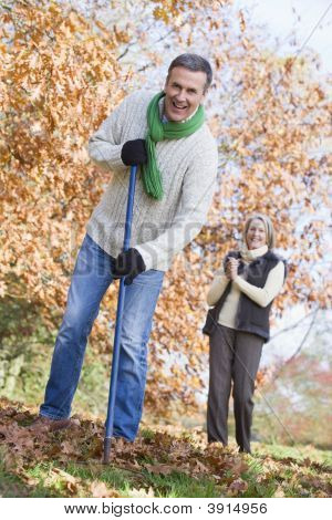 Man Raking Leaves With Wife In Background