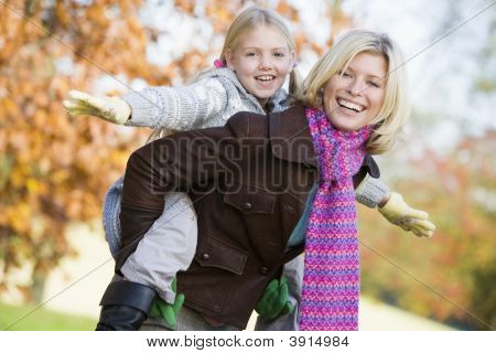 Woman With Child On Back In Woodland