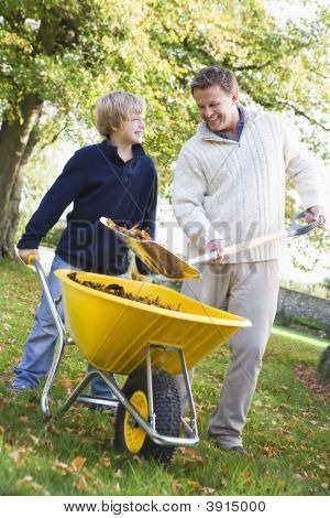 Man And Child Putting Leaves Into A Wheelbarrow