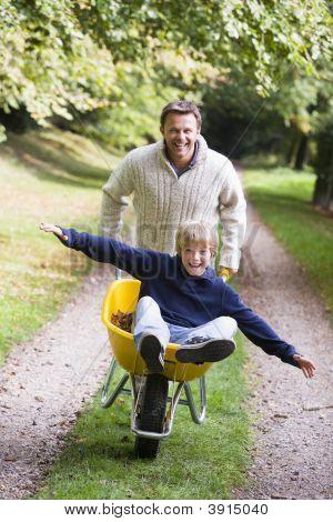 Man Pushing Boy In Wheelbarrow