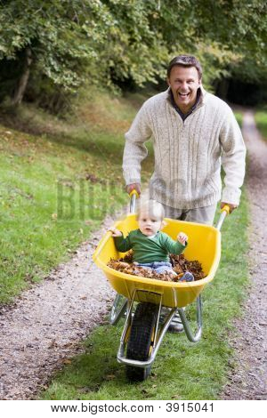 Man Pushing Baby In Wheelbarrow