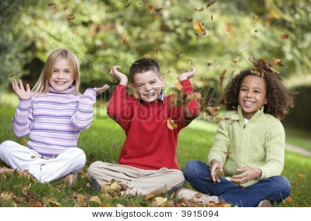 Children Sitting On Grass Throwing Leaves