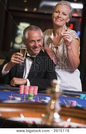 Couple Paying Roulette With Champagne