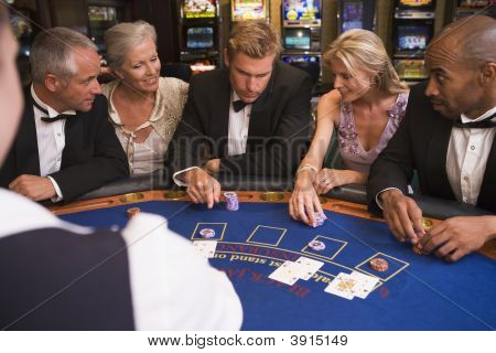 Group Of Adults Playing Cards In Casino