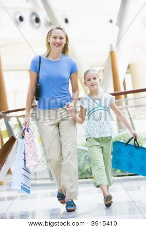 Woman And Daughter In Shopping Mall With Bags