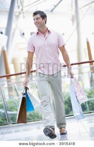 Homem no shopping com sacos