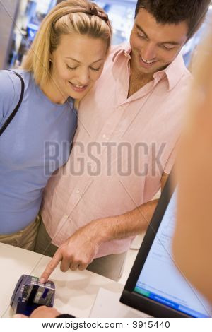 Couple Paying With Card In Shop