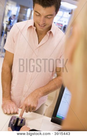 Man Putting In Pin Number In Shop