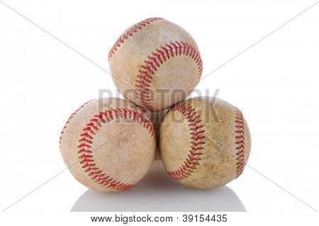 Closeup of a stack of well used baseballs. Horizontal format on a white background with reflection.