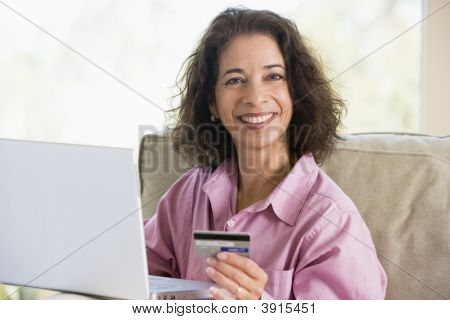 Woman Paying With Card Over Internet At Home