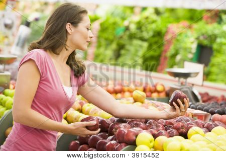 Mulher escolhendo frutas em loja