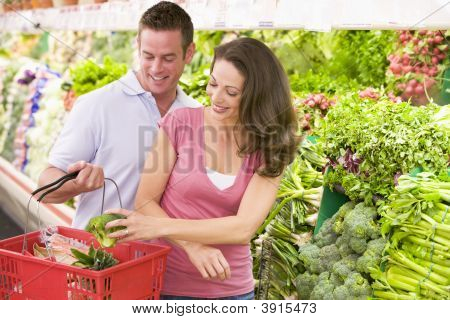 Couple Choosing Vegetables In Shop