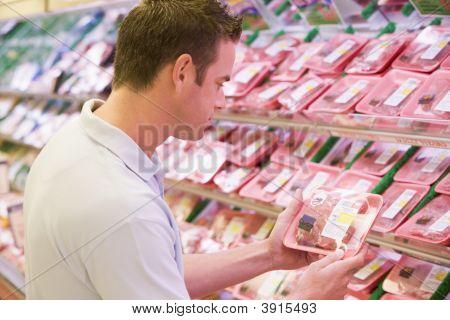 Man Choosing Meat From Shop