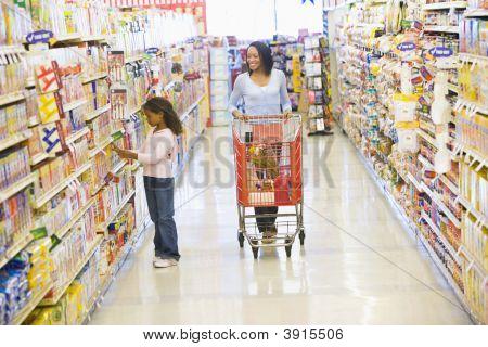 Mujer y niño empujando el carro en el supermercado