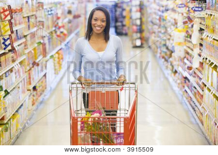 Woman Pushing Trolley In Supermarket