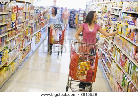 Women Pushing Trolleys In Supermarket