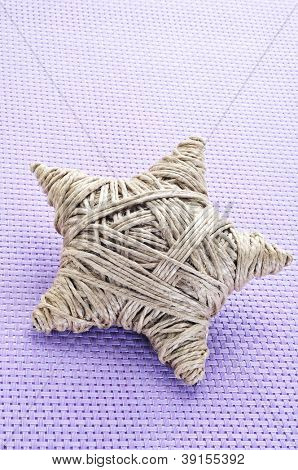 a christmas star made with hemp twine on a violet woven background