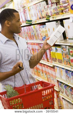 Man Reading Packet In Supermarket