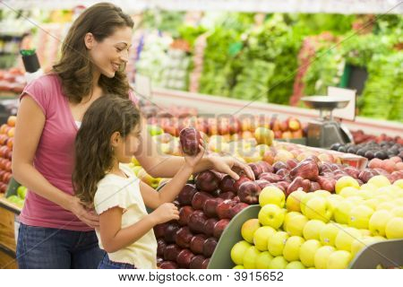 Mujer y niño elegir fruta en tienda