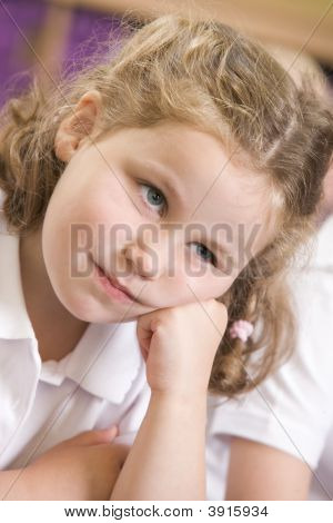 Portrait Of Child Day Dreaming On Carpet In Classroom