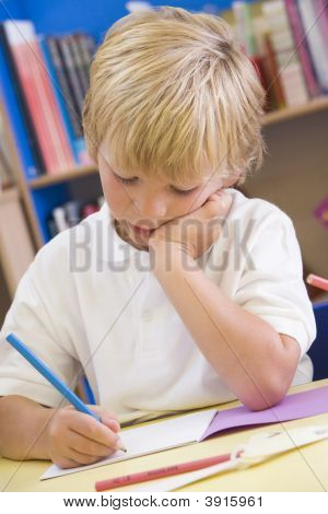 Portrait Of Child Working At Desk In Classroom