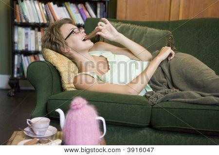 Woman Eating Chocolate On Sofa