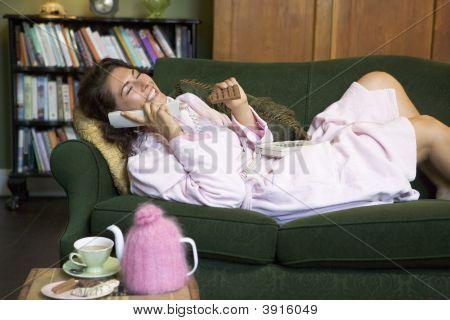 Mulher sentou-se no sofá com o telefone e Chocolate