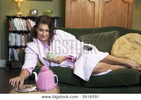Woman Sat Eating And Drinking On Sofa