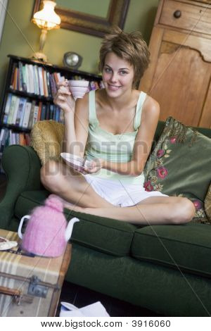 Woman Smiling With Tea Cup On Sofa