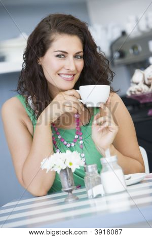 Woman Sat At Table Drinking Tea