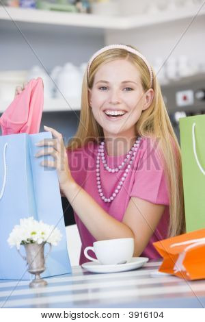 Woman Showing Off Purchases In Tea Room