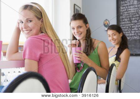 Women Sat On Stools In CafŽ Drinking