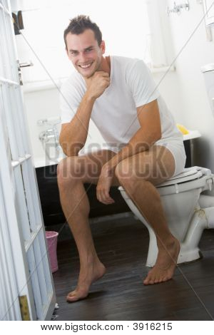Man Sat On Toilet Seat In Bathroom