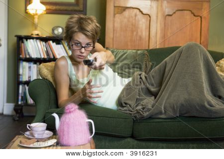 Woman Laid On Sofa With Remote Control In Hand